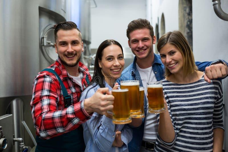 Brouwers die bieren roosteren bij brouwerij stock fotografie
