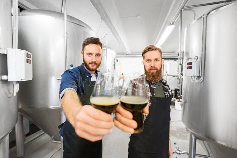 Brouwers die glazen ambachtbier clinking bij brouwerij stock foto's