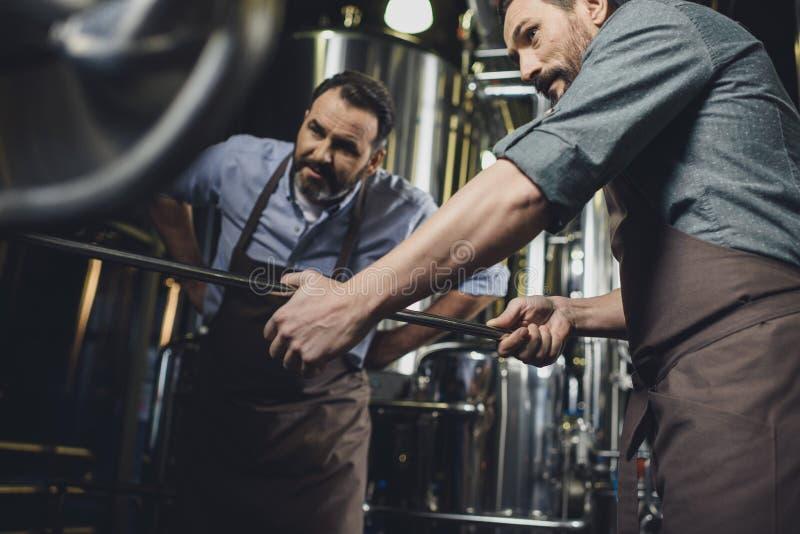 Brouwers die met industrieel materiaal werken stock foto
