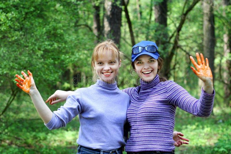 Brovary Украина 08 05 2006 2 молодых усмехаясь красивых девушек с поднятыми пакостными оранжевыми руками на природе после варить  стоковая фотография rf