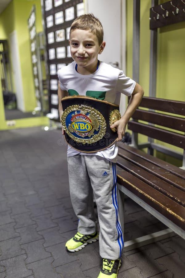 Brovary De Oekraïne, 14 11 2015 probeert het glimlachen weinig jongen op een kampioens in dozen doende riem royalty-vrije stock fotografie