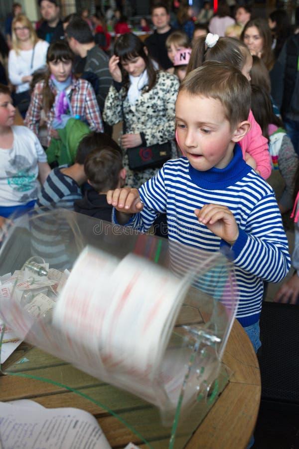 Brovary ucrânia 25 04 2015 Uma menina está olhando fixamente na caixa de giro com bilhetes de loteria foto de stock