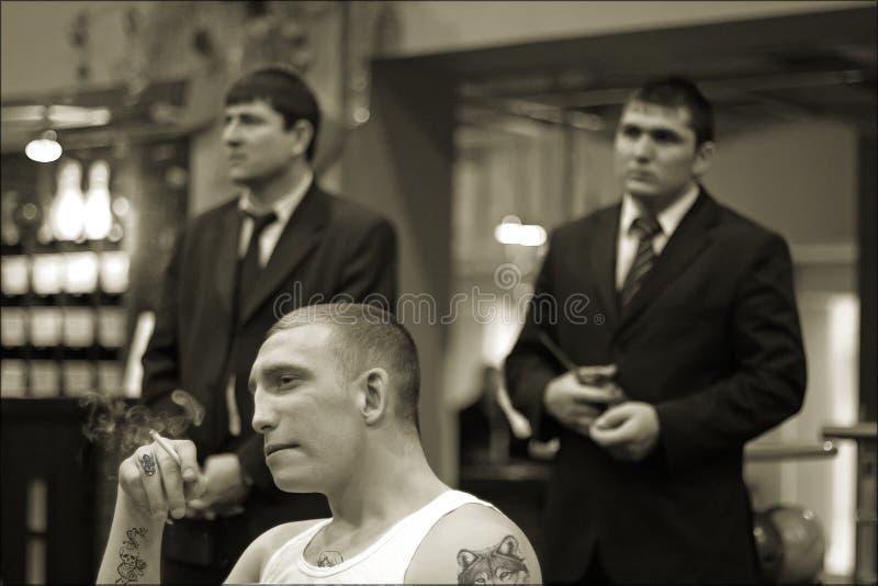 Brovary, Ucrania, 22 02 2006 tatuajes del hombre en la cárcel están fumando Dos sus guardias colocarse detrás fotos de archivo