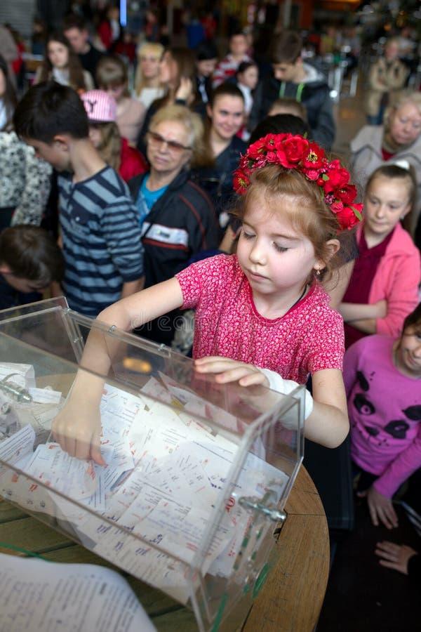 Brovary ukraine 25 04 2015 Ein kleines Mädchen mit schließenden Augen geht einen Lottoschein aus dem Kasten heraus hinaus lizenzfreie stockbilder
