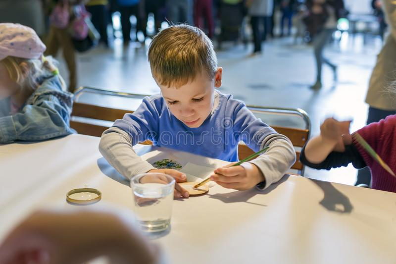 Brovary.Ukraine. 25.04.2015 A little boy is painting with the brush on the paper stock photo