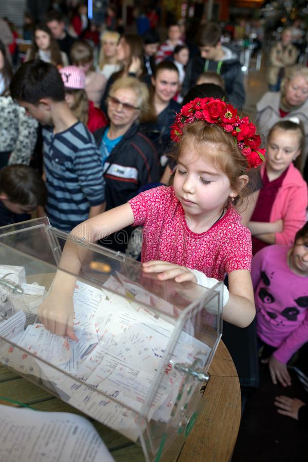 Brovary. Ukraine.. 25.04.2015. A little girl with closing eyes is getting out a lottery ticket out of the box. Other children observe royalty free stock images