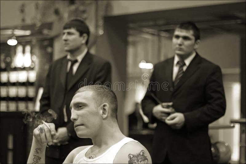 Brovary, Ukraine, 22.02.2006 Man in prison tattoos is smoking. Two his guards stand behind. Inside stock photos