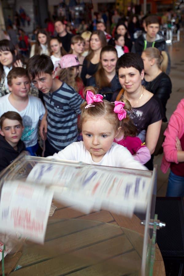 Brovary ukraine Vermaakcentrum 25 04 2015 Een klein meisje staart bij de het draaien doos met loterijkaartjes stock afbeeldingen