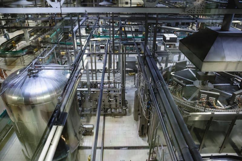 Browarniana produkcja, warsztat z stalowymi zbiornikami, drymby i maszyneria przy nowożytną piwną fabryką, obraz royalty free