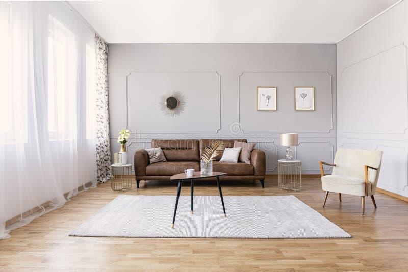 Brown überziehen Sofa im Wohnzimmerinnenraum mit stilvollem Lehnsessel, Couchtisch und Zeichnungen mit Leder lizenzfreies stockbild