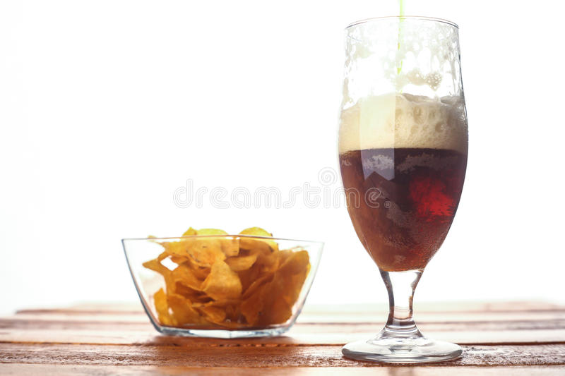 Brown ale pouring. Into a tall glass standing on a wooden table with potato chip snack and bright background stock photo