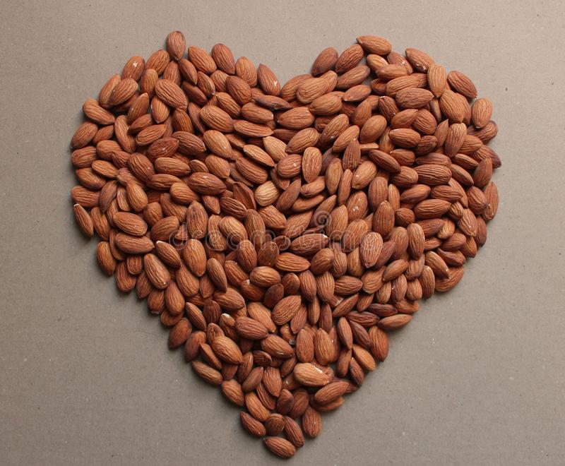 Brown almond nuts background heart. Brown almond nuts backdround heart with love for Valentine`s Day stock photography