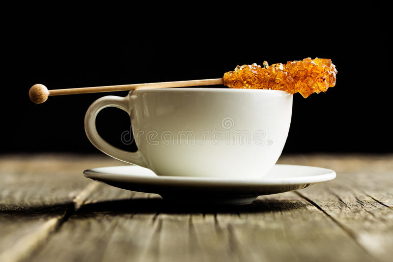 Brown amber sugar crystal on wooden stick and coffee cup. Brown amber sugar crystal on wooden stick and coffee cup on old wooden table stock photos