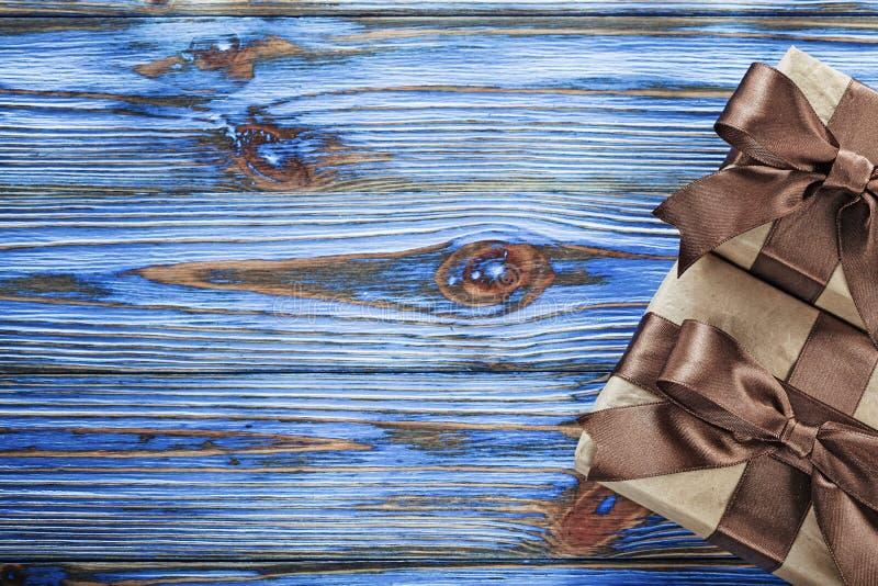 Brown apresenta caixas com as fitas na placa de madeira do vintage fotografia de stock royalty free