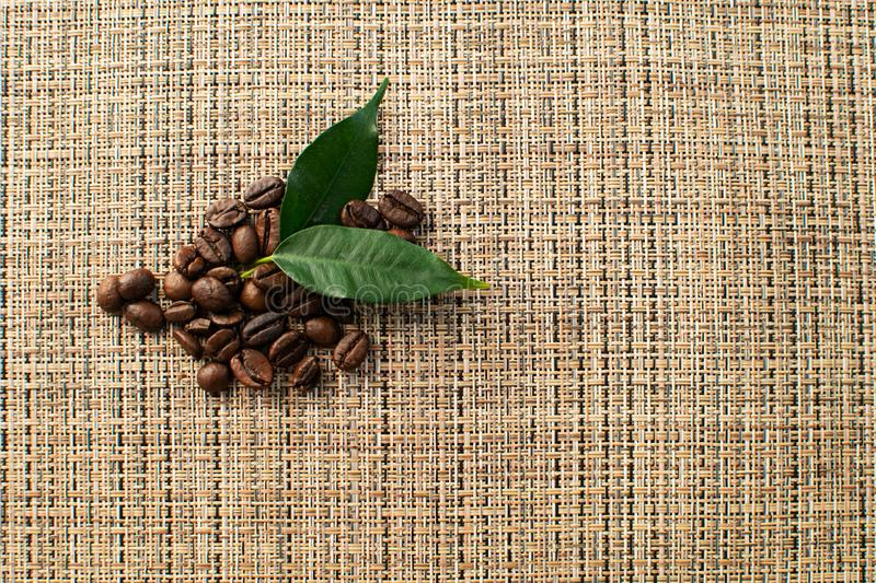 Brown arabica coffee beans with leaf on brown background. Shiny fresh roasted arabica coffee beans with green leaf on brown background stock photography