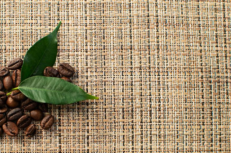 Brown arabica coffee beans with leaf on brown background. Shiny fresh roasted arabica coffee beans with green leaf on brown background stock images