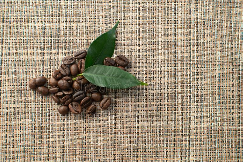 Brown arabica coffee beans with leaf on brown background. Shiny fresh roasted arabica coffee beans with green leaf on brown background royalty free stock photos