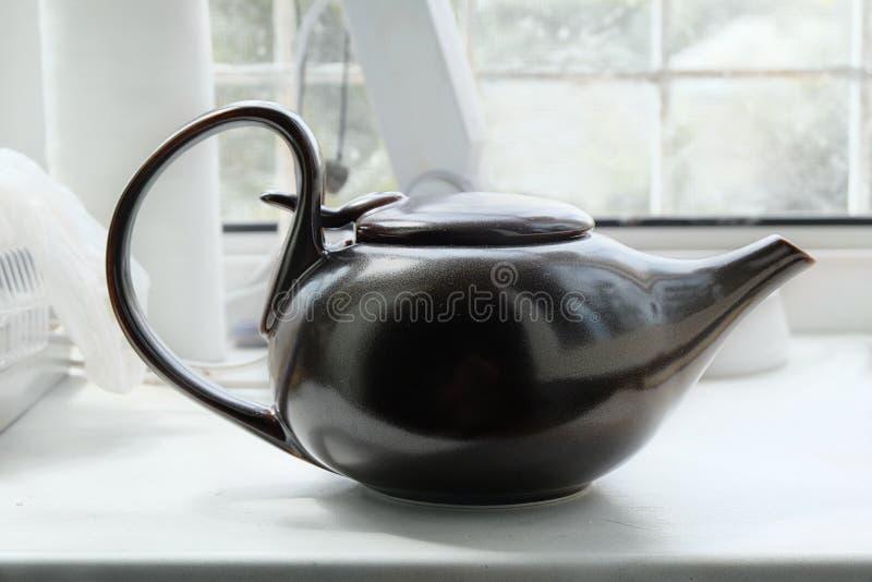 Brown azjatykci teapot na białym windowsill zdjęcie stock