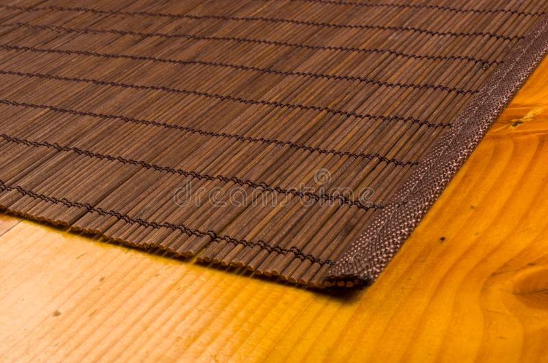 Bamboo Mat - stand food, close-up, wooden background. Brown bamboo Mat - stand food, close-up, macro, wooden background stock photo