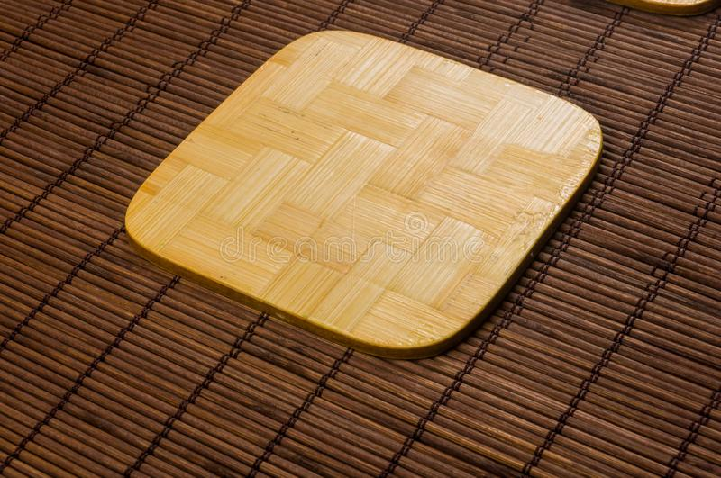 Bamboo Mat - stand food with bamboo stands for hot, close-up, wooden background. Brown bamboo Mat - stand food with bamboo stands for hot, close-up, macro stock photo