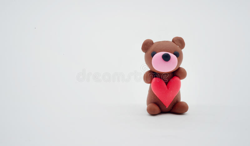 Brown bear doll show red heart on white background. For valentine`s day royalty free stock photos