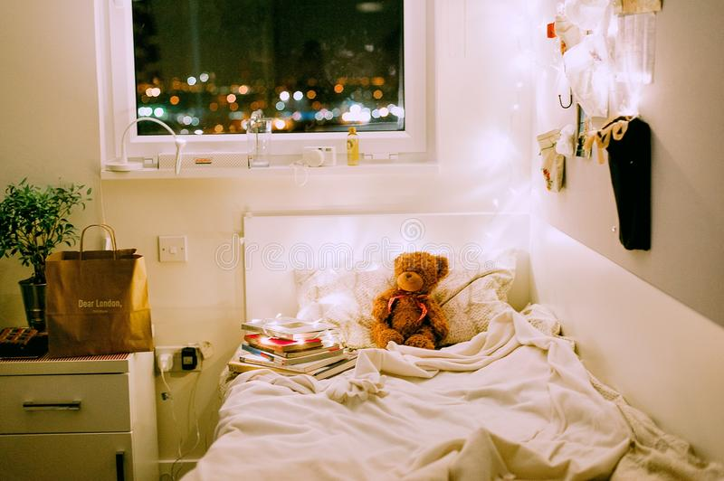 Brown Bear Plush Toy on White Bed Comforter Inside Lighted Bedroom royalty free stock images