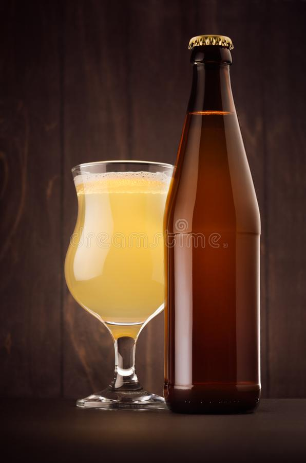 Brown beer bottle NRW and glass tulip with muddy weizen on dark wood board, vertical, mock up. Template for advertising, design, branding identity royalty free stock photo