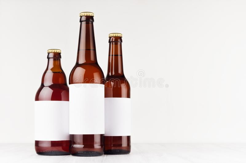Brown beer bottles collection different type with blank white label on white wooden board, mock up. stock photography