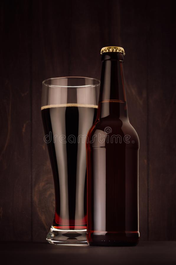 Brown beer longneck bottle and glass weizen with porter on dark wood board, vertical, mock up. Template for advertising, design, branding identity stock image