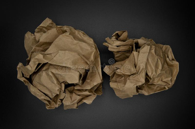Brown and beige crumpled paper ball. Isolated on black background stock photo