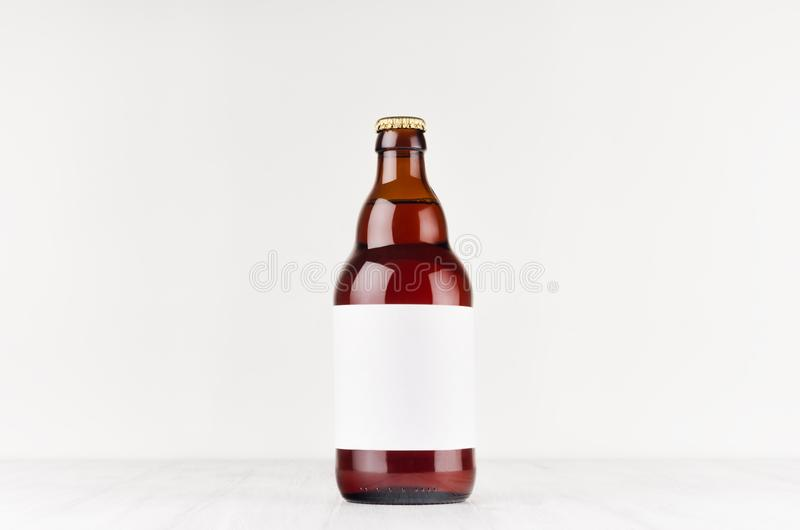 Brown belgian steinie beer bottle 500ml with blank white label on white wooden board, mock up. stock images