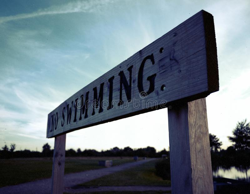 Brown and Black Wooden No Swimming Signage royalty free stock photography