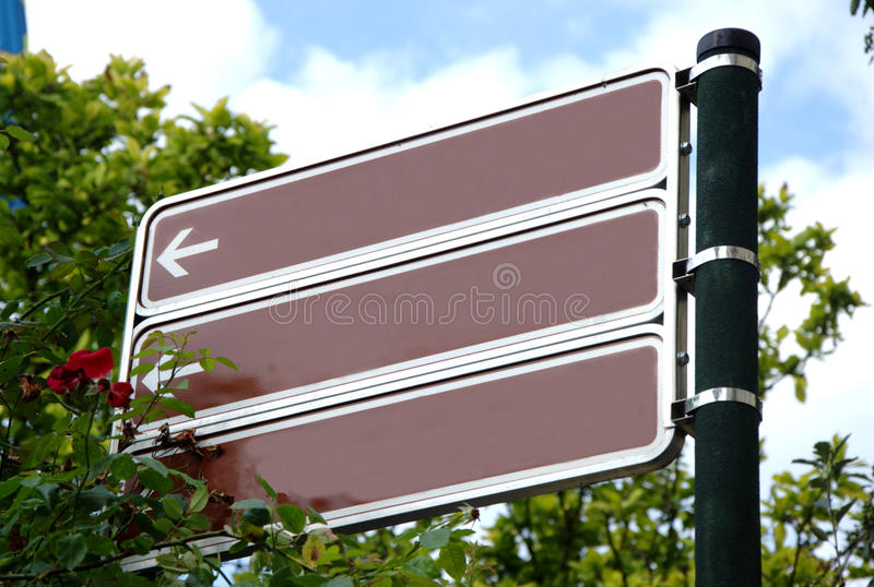 Brown blank direction signs with rose and green trees royalty free stock photography