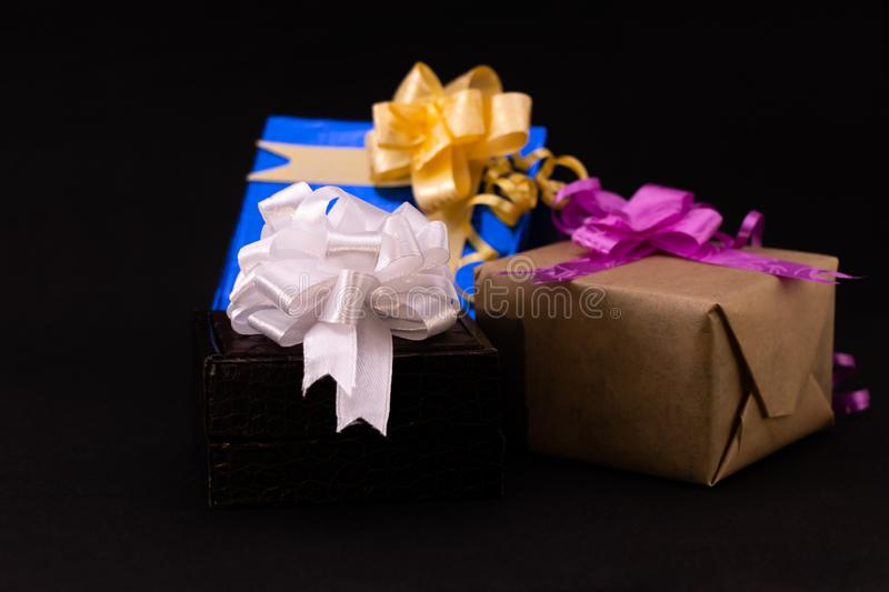 Brown and blue gift box decorated with colorful ribbons on black background royalty free stock photo