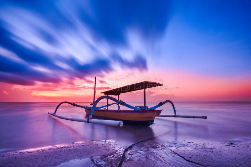 Brown Blue and White Wooden Boat during Orange Sunset royalty free stock images