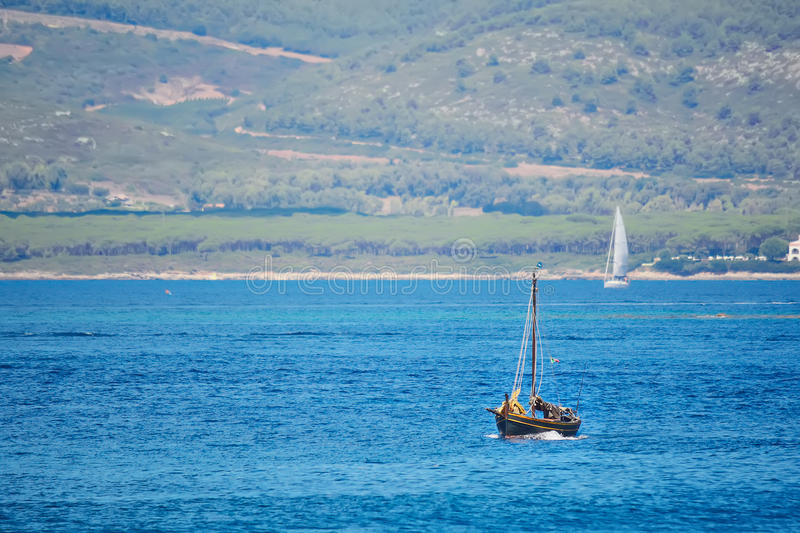 Brown boat in the blue sea. Shot in Sardinia, Italy royalty free stock photo