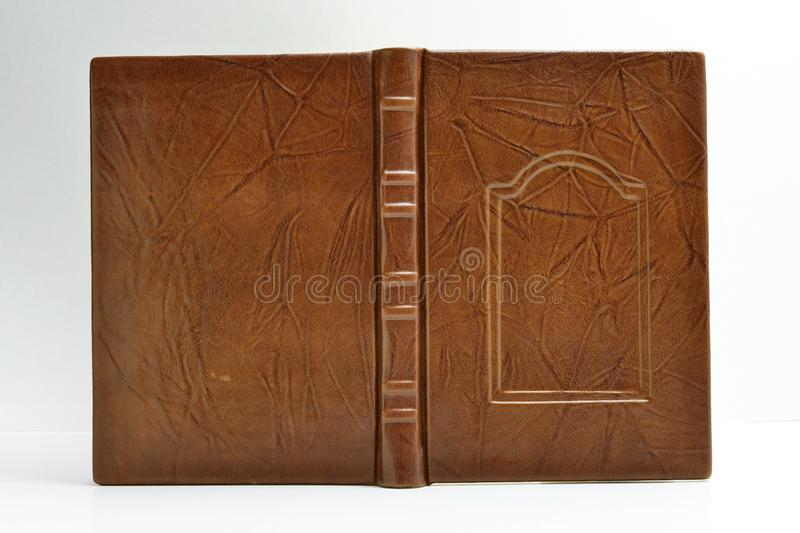 Brown book cover bound in leather with wrinkles all around the surface captured opened and isolated.  stock photos