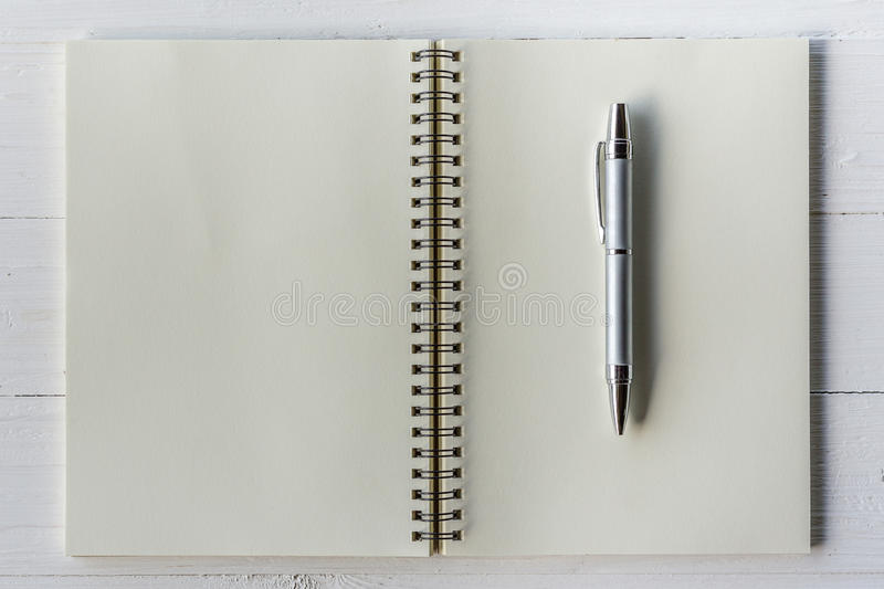 Brown book open and pen on wood table royalty free stock photography