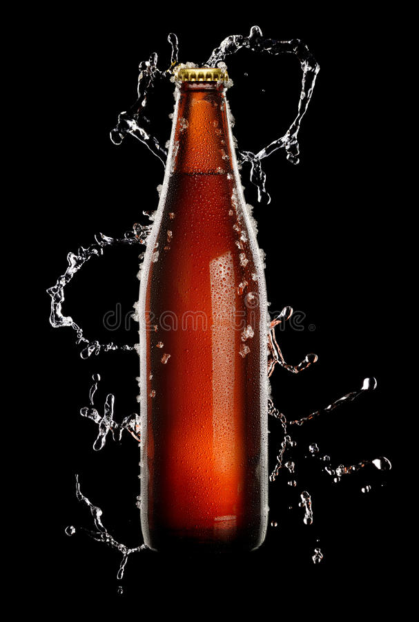 Brown bottle of beer. Cold brown bottle of beer with water droplets and ice over black background in splash of water stock images
