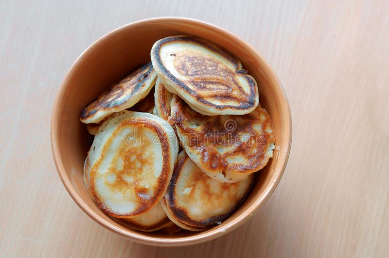 Brown bowl full of pancakes stock photography