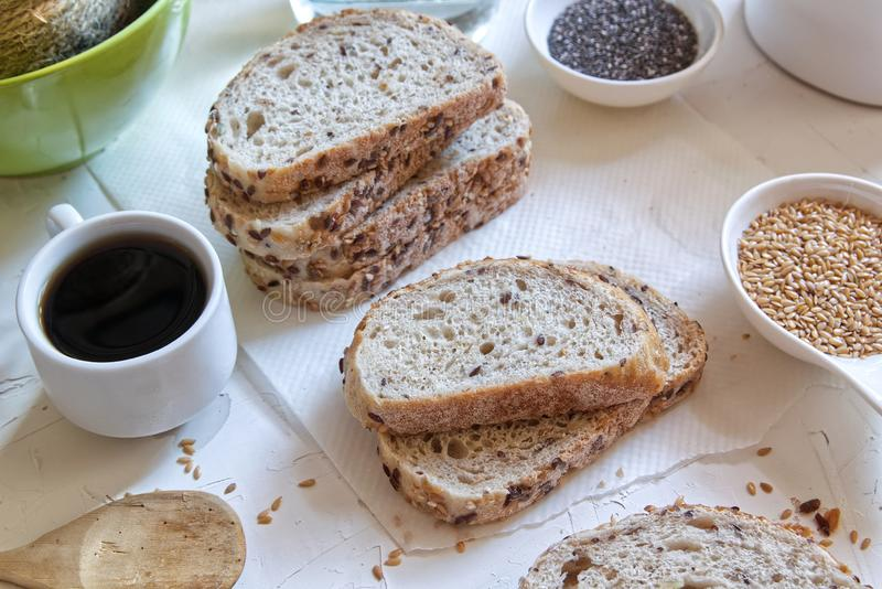Brown bread with cereals next to a coffee cup on a white wooden table of a rustic kitchen. Seeds and ingredients stock photography