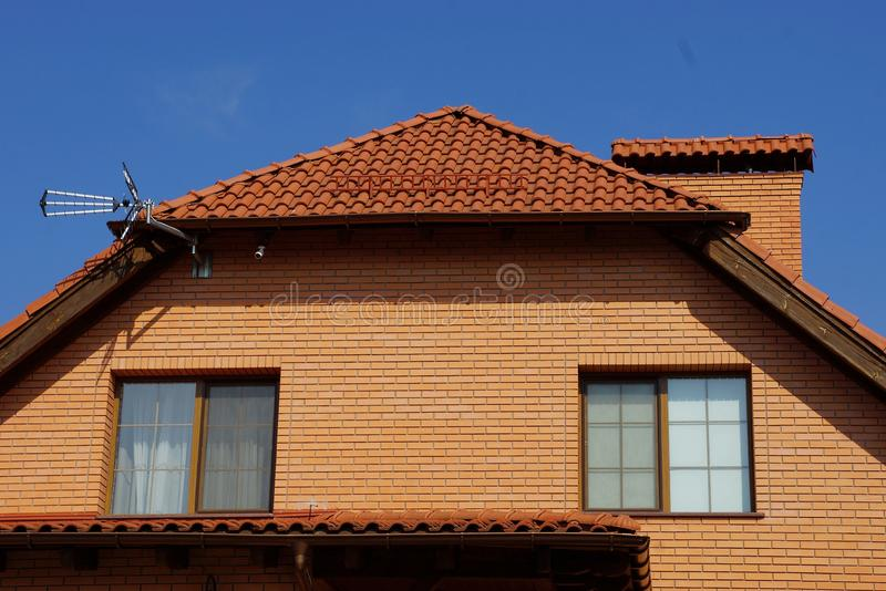 Brown brick attic with windows under a tiled roof with a chimney. Against the blue sky stock images