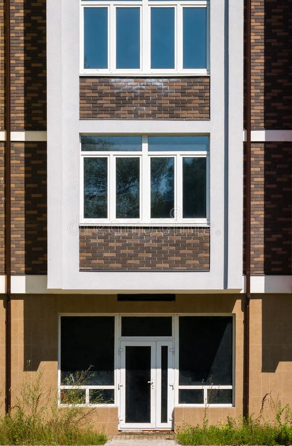 Brown brick house with white windows. Fragment of brown brick house with white windows and entrance door royalty free stock images