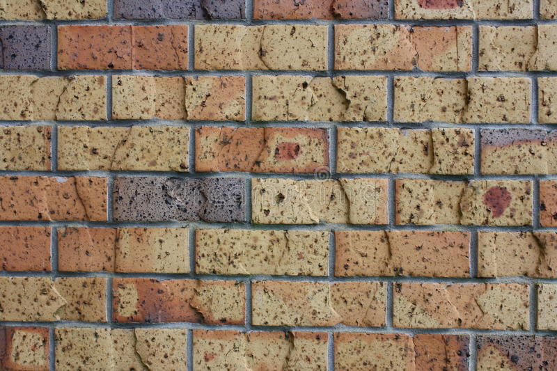 Brown Brick Wall. Brown and grey brick wall with different shades of brown and grey bricks of a church building stock photo