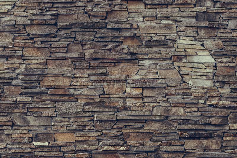Brown brick wall. Stone weathered backdrop, granite facade surface, rock textured. Decorative dirty tiles on the wall. Grunge urba stock photo