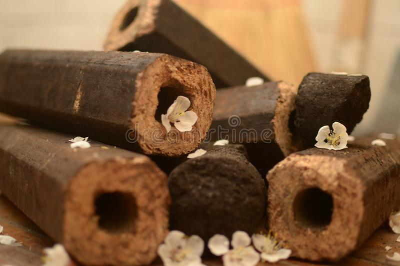 Octagonal brown briquette with a hole. Brown briquette octagonal witha a hole and worth of coal in a heap on the floor with petals of white flowers and a broom royalty free stock photos