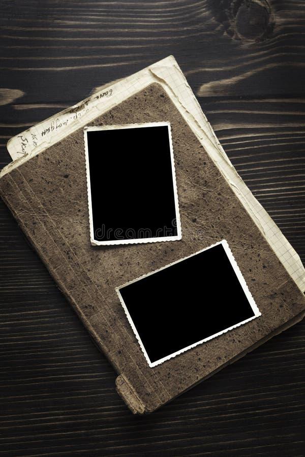 Brown-Buch mit altem Rahmenfoto auf hölzernem Tabellenhintergrund lizenzfreie stockfotos