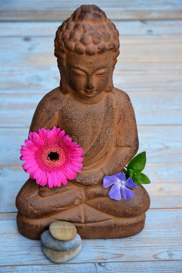 Brown Buddha statue with flowers and zen stones. On old wood royalty free stock photography