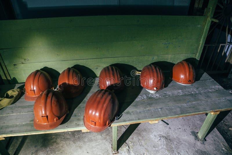 Brown budowniczego ` s zbawczy hełmy na zielonej ławce zdjęcie stock
