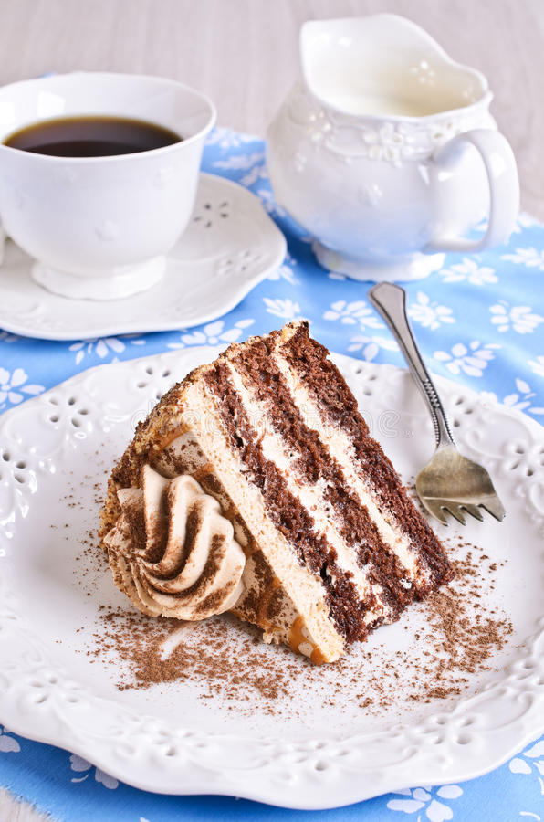 Brown cake with cream. Cut a piece of cake brown with cream on the plate royalty free stock photo